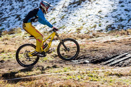 Cyclist on the downhill on snow and mud photo