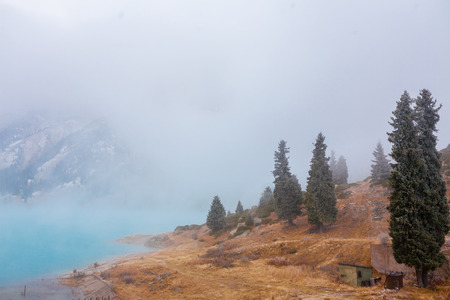 Mountain Lake is drowning in thick fog photo