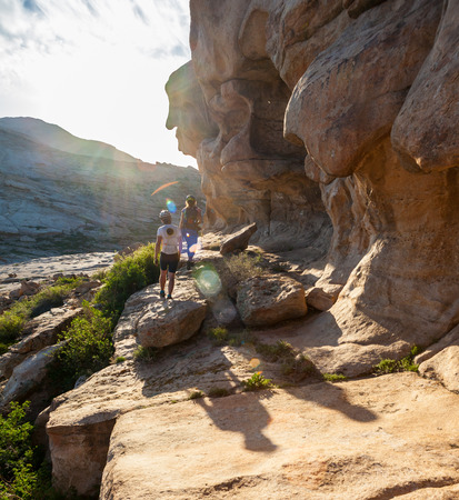 contemplates: People in the mountains contemplates stone landscape at sunset Stock Photo