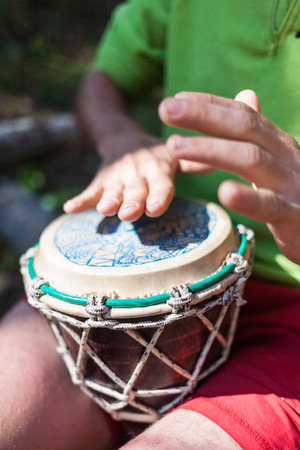 Man playing the hand drums in nature