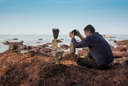 builds: man builds the stones on each other on the beach