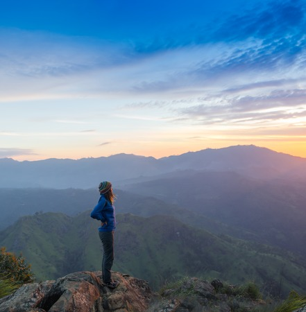 reached: Happy celebrating winning success woman at sunset or sunrise standing elated with arms raised up above her head in celebration of having reached mountain top summit goal during hiking travel trek.
