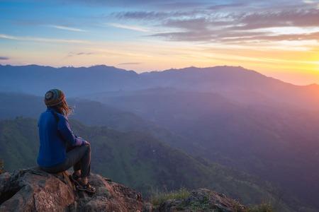 Celebrando feliz ganadora Éxito de la mujer al atardecer o amanecer pie eufórico con los brazos levantados por encima de la cabeza en la celebración de haber llegado a la montaña meta cumbre superior durante senderismo viajar viaje.