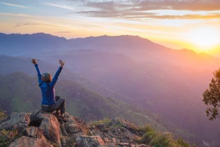 慶典: 快樂慶祝獲勝成功女人在日落或日出站在興高采烈,在慶祝徒步旅行跋涉期間已達到山頂首腦會議的目標提出了在她頭頂的武器。 版權商用圖片