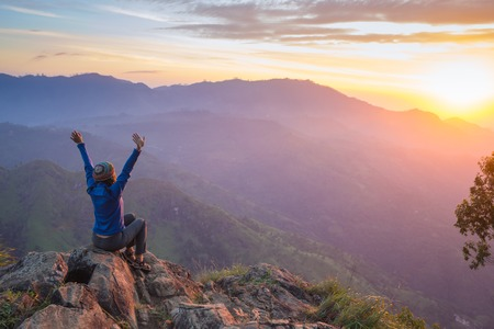 adventures: Happy celebrating winning success woman at sunset or sunrise standing elated with arms raised up above her head in celebration of having reached mountain top summit goal during hiking travel trek.