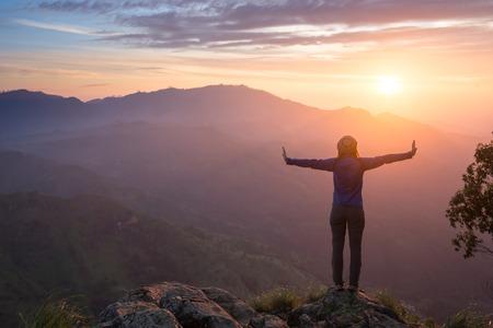 Célébrer heureux gagnant succès femme au coucher du soleil ou le lever debout exalté avec les bras levés au-dessus de sa tête dans la célébration d'avoir atteint montagne objectif prioritaire du sommet au cours de la randonnée trek Voyage.