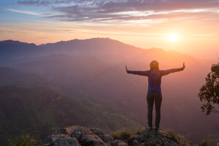 arms above head: Happy celebrating winning success woman at sunset or sunrise standing elated with arms raised up above her head in celebration of having reached mountain top summit goal during hiking travel trek.