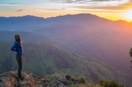 Gelukkig vieren het winnen van succes vrouw bij zonsondergang of zonsopkomst staan opgetogen met opgeheven armen boven haar hoofd in de viering van de berg top top doel te hebben bereikt tijdens het wandelen trek.
