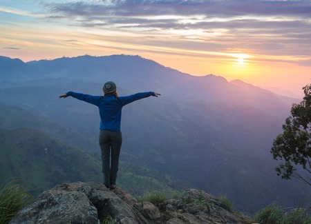 mountains and sky: Happy celebrating winning success woman at sunset or sunrise standing elated with arms raised up above her head in celebration of having reached mountain top summit goal during hiking travel trek.