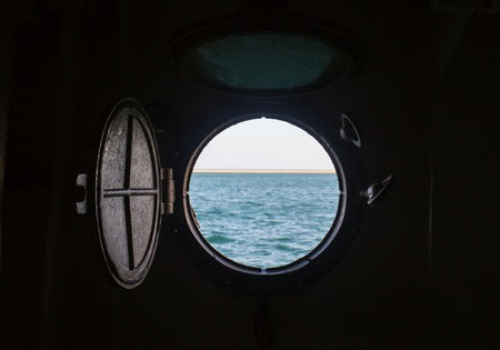ship porthole on wooden wall on the boat