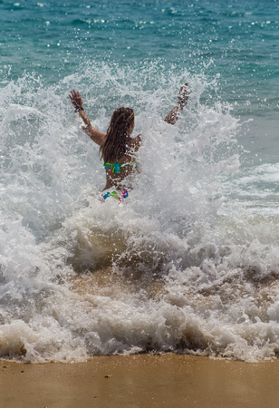 summer vacation bikini: girl laughing and crying in the spray of waves at sea on a sunny  day