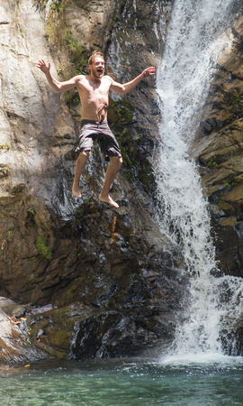 large rock: jumping into a waterfall with a large rock in the jungle