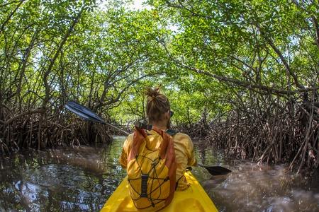 ocean kayak: Jovencita remando con fuerza el kayak de mar con una gran cantidad de salpicaduras