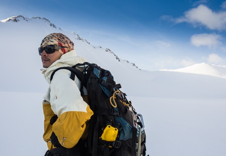 Mountaineer reaches the top of a snowy mountain in a sunny winter day. Alps, Italy. Standard-Bild