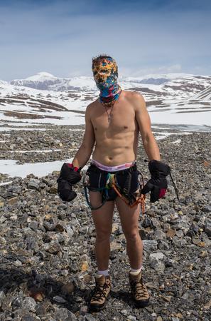 Mann in der Badehose, aber mit Kletterausrüstung