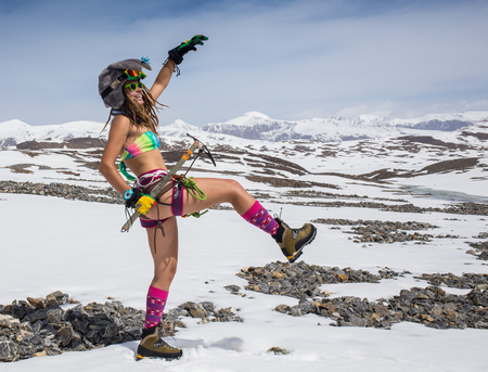 winter fashion: The girl in a bathing suit in the mountains but  climbing equipment Stock Photo