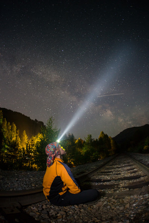torchlight: A hiker at night, wearing a head torch in a forest,under a starry sky. Stock Photo