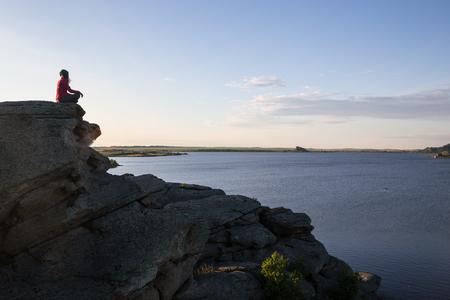 Young woman sitting on rock and enjoying  beautiful view Standard-Bild