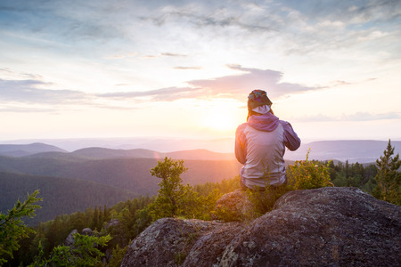 Young woman sitting on a rock with backpack and looking to the horizon 스톡 콘텐츠