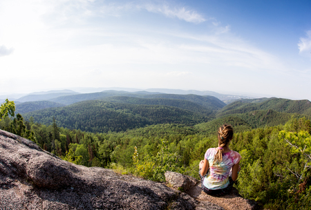 Young woman sitting on a rock with backpack and looking to the horizon Standard-Bild