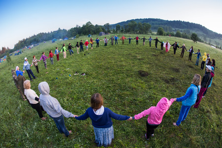Cosmos Village, Almaty Province, Kazakhstan - 16 August 2015: Large group of happy peoples play roundelay and stand in circle in the park on the green grass on sunny summer day, view from aboveThe festival of ethnic music Forey, a lot of people gathers on Redakční