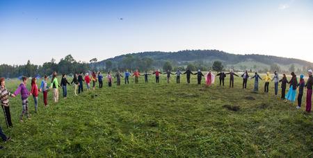 circulo de personas: Cosmos Village, Provincia de Almaty, Kazajstán - 16 de agosto de 2015: Gran grupo de pueblos felices jugar con estribillo y de pie en círculo en el parque en la hierba verde en día soleado de verano, vista desde abovethe festival de música étnica Forey, un montón de gente se reúne en Editorial