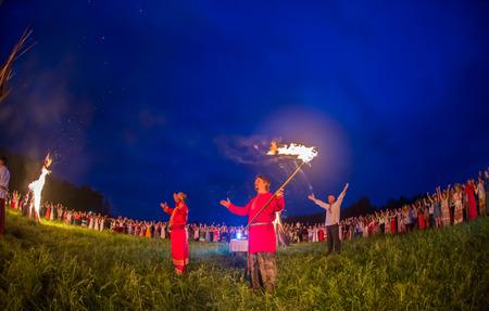 resplandor: Cosmos Village, Provincia de Almaty, Kazajstán - 16 de agosto de 2015: La gente celebra el día de fiesta y el baile de Rusia en un círculo alrededor del fuego sagrado. El festival de música étnica Forey, un montón de gente se reúne en estas vacaciones para relajarse y divertirse. Ope étnico