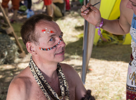 aborigines: White male dressed in African aborigines with a tambourine at the festival of colors
