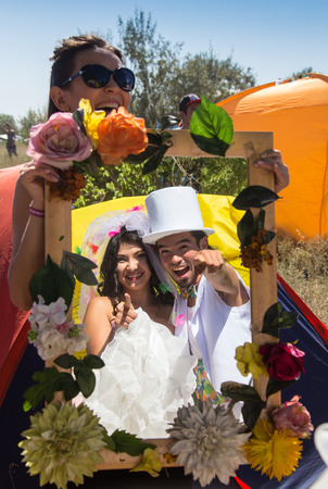 ethnic festival: Happy couple on a crazy wedding on ethnic festival. Young newlyweds clinking glasses and enjoying romantic moment together at wedding reception outside Stock Photo