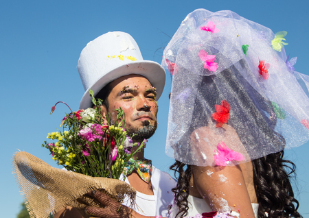 festival moment: Happy couple on a crazy wedding on ethnic festival. Young newlyweds clinking glasses and enjoying romantic moment together at wedding reception outside Stock Photo