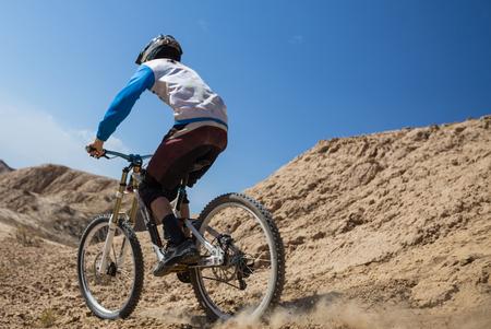Young man on a mountain bike riding and relaxing in Charyn canyon,  Kazakhstan Standard-Bild