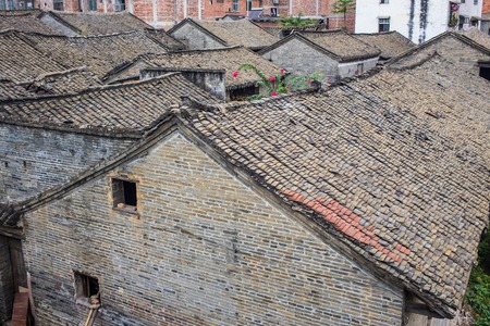 barrel tile: Red tile roof, aka Spanish or Mission clay tiles house under construction nearby, others on mountain in Weathered tiles show their age in suburban  Carmen de Guzho