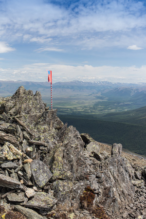 red flag flying in the background of the mountains.