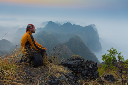 높은 산의 돌 위에 앉아하는 남자.