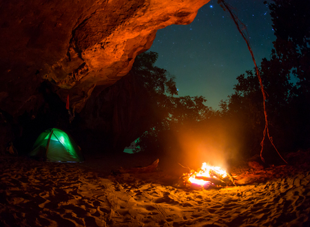 bonfire night: Tent camping car couple romantic sitting by bonfire night countryside. Stock Photo