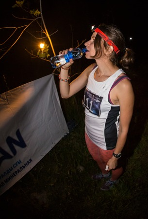 work took: KAZAKHSTAN, ALMATY - 09 JULY 2016: Night trail running competitionsTunRun that took place in the tract Kok Zhailau. Beautiful fitness athlete woman drinking water after work out exercising on sunset evening summer in beach outdoor portrait