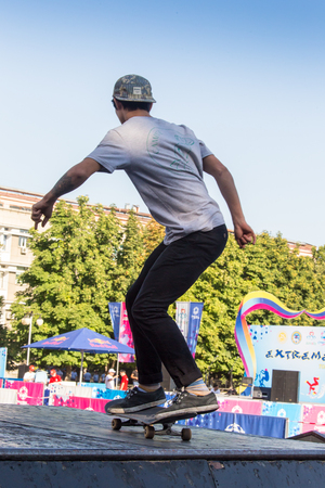 KAZAKHSTANALMATY - AUGUST 28, 2016: Urban extreme competition, where the city athletes compete in the disciplines: skateboard, roller skates, BMX. Skateboarder doing a trick in skate park.