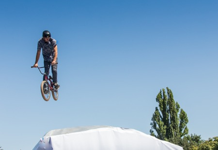 KAZAKHSTAN ALMATY - AUGUST 28, 2016: Urban extreme competition, where the city athletes compete in the disciplines: skateboard, roller skates, BMX. Bmx stunt performed at the top of a mini ramp on a skatepark