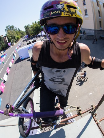 KAZAKHSTAN ALMATY - AUGUST 28, 2016: Urban extreme competition, where the city athletes compete in the disciplines: skateboard, roller skates, BMX. Bmx stunt performed at the top of a mini ramp on a skatepark.Portrait of Middle Age Alpine Climber Face of