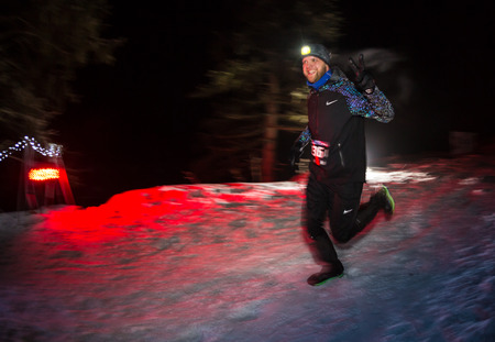 ALMATY, KAZAKHSTAN - 18 FEBRUARY 2017: Night competitions in the foothills of the city of Almaty, in the Trailrunning and Skyship discipline, which is called TunRun winter edition. Man running in the mountains at night Editorial