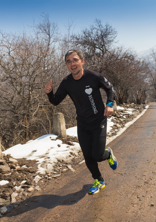 foothills: ALMATY, KAZAKHSTAN - APRIL 09, 2017: Amateur competitions - Mountain half-marathon, in the foothills of Almaty, on the Yunat lakes. Athletic young man running in the nature. Healthy lifestyle
