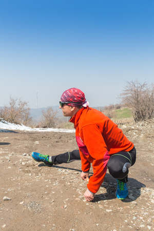 ALMATY, KAZAKHSTAN - APRIL 09, 2017: Amateur competitions - Mountain half-marathon, in the foothills of Almaty, on the Yunat lakes. Portrait of a male athlete warming up and stretching Editorial