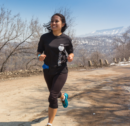 ALMATY, KAZAKHSTAN - APRIL 09, 2017: Amateur competitions - Mountain half-marathon, in the foothills of Almaty, on the Yunat lakes. runner - woman running outdoors training for marathon run. Beautiful fit asian fitness model in her 20s.