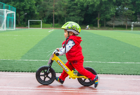 become: KAZAKHSTAN, ALMATY - JUNE 11, 2017: Childrens cycling competitions Tour de kids. Children aged 2 to 7 years compete in the stadium and receive prizes. A little boy rides a bike and competes to become a winner.