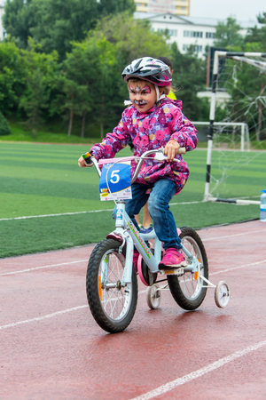KAZAKHSTAN, ALMATY - JUNE 11, 2017: Childrens cycling competitions Tour de kids. Children aged 2 to 7 years compete in the stadium and receive prizes. The girl on a bicycle rides on a sports stadium and competes to win.