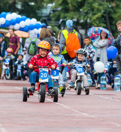 KAZAKHSTAN, ALMATY - JUNE 11, 2017: Childrens cycling competitions Tour de kids. Children aged 2 to 7 years compete in the stadium and receive prizes. Portrait of three little cyclists riding their bikes