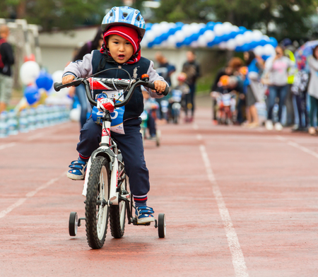 KAZAKHSTAN, ALMATY - JUNE 11, 2017: Childrens cycling competitions Tour de kids. Children aged 2 to 7 years compete in the stadium and receive prizes. A little boy rides a bike and competes to become a winner.