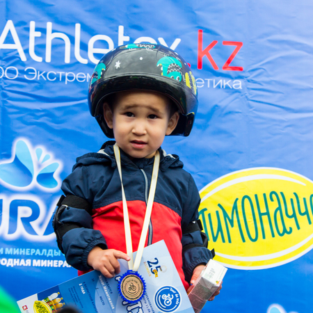 compete: KAZAKHSTAN, ALMATY - JUNE 11, 2017: Childrens cycling competitions Tour de kids. Children aged 2 to 7 years compete in the stadium and receive prizes. Excited boy and girls with medals
