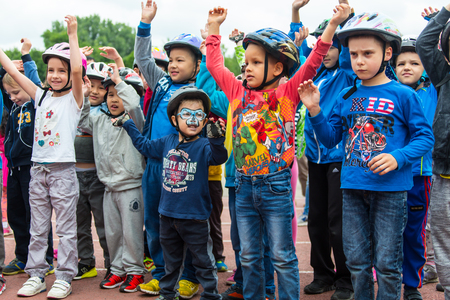 compete: KAZAKHSTAN, ALMATY - JUNE 11, 2017: Childrens cycling competitions Tour de kids. Children aged 2 to 7 years compete in the stadium and receive prizes. Children at the solemn construction - waiting for the start of the competition.