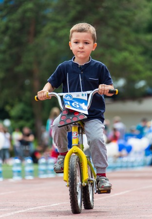 KAZAKHSTAN, ALMATY - JUNE 11, 2017: Childrens cycling competitions Tour de kids. Children aged 2 to 7 years compete in the stadium and receive prizes. Portrait of a cute boy on bicycle